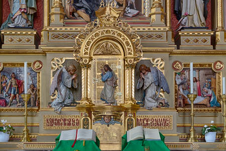 Sacred altar from the Parish Church of Urtijëi in Italy where wood carved statue of Jesus Christ between two angels is standing at a golden door and knocking as in sentence from Apocalypse book. Open books in foreground