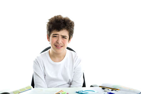 sadly: Cute Caucasian smooth-skinned boy sadly sitting in front of homework wearing a white long sleeve t-shirt