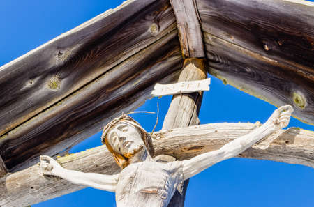 crucify: A wood carved statue  of the Crucifixion of Jesus Christ on top of the dolomites alps Stock Photo
