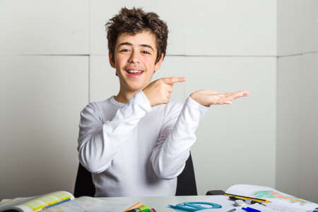 Caucasian latin young boy sits in front of homework, smiles in a trustable manner  and with index finger indicates something he's bringing on his left hand on industrial background
