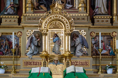 book of revelation: Sacred altar from the Parish Church of Urtijëi in Italy where wood carved statue of Jesus Christ between two angels is standing at a golden door and knocking as in sentence from Apocalypse book. Open books in foreground