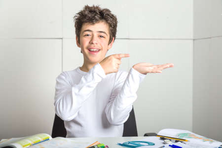 trustable: Caucasian smooth-skinned boy sits in front of homework, smiles in a trustable manner  and with index finger indicates something he's bringing on his left hand on industrial background