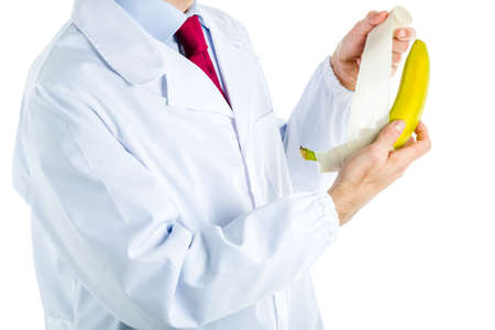 erectile: Caucasian male doctor dressed in white coat, blue shirt and red tie is bandaging a banana