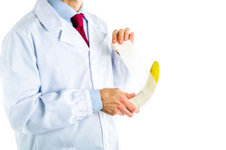 Caucasian male doctor dressed in white coat, blue shirt and red tie is bandaging a yellow banana