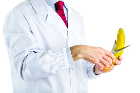Caucasian male doctor dressed in white coat, blue shirt and red tie is cutting a banana with scissors