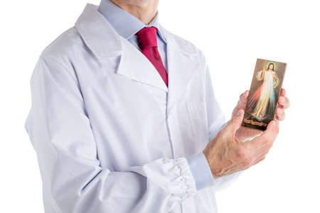 merciful: Caucasian male doctor dressed in white coat, blue shirt and red tie is holding Merciful Jesus wooden icon Stock Photo