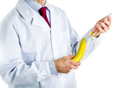 erectile: Caucasian male doctor dressed in white coat, blue shirt and red tie is making an injection to a banana with a syringe full of pills