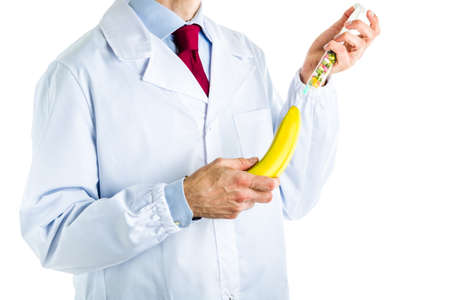 impotence: Caucasian male doctor dressed in white coat, blue shirt and red tie is making an injection to a banana with a syringe full of pills