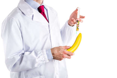 erection: Caucasian male doctor dressed in white coat, blue shirt and red tie is making an injection to a banana with a syringe full of pills