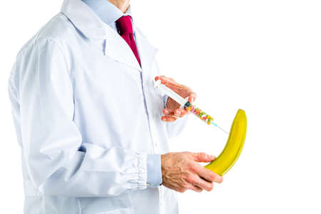 Caucasian male doctor dressed in white coat, blue shirt and red tie is making an injection to a banana with a syringe full of pills