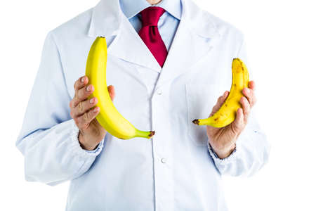 dysfunction: Caucasian male doctor dressed in white coat, blue shirt and red tie is showing big and small bananas