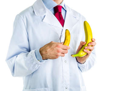 Caucasian male doctor dressed in white coat, blue shirt and red tie is showing big and small bananas
