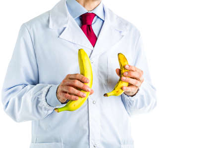 erectile: Caucasian male doctor dressed in white coat, blue shirt and red tie is showing big and small bananas