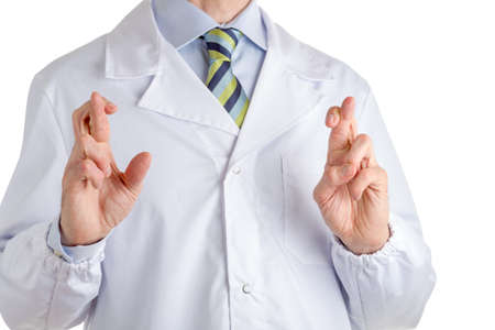 superstitious: Man dressed with medical white coat, light blue shirt and glossy regimental tie with dark blue, light blue and green stripes, is crossing fingers as superstitious gesture