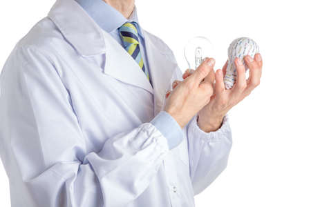 white coat: Man dressed with medical white coat, light blue shirt and glossy regimental tie with dark blue, light blue and green stripes, is holding  a 3d print lightbulb and a real one