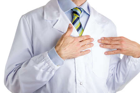 medical attention: Man dressed with medical white coat, light blue shirt and glossy regimental tie with dark blue, light blue and green stripes, is pointing to his chest with both hands, driving attention to his heart