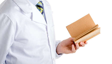 white coat: Man dressed with medical white coat, light blue shirt and glossy regimental tie with dark blue, light blue and green stripes, is reading a blank cork book