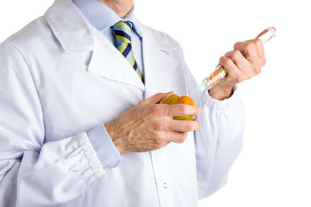 white coat: bust of a man wearing medical white coat, light blue shirt and glossy regimental tie white dark blue, light blue and green stripes, and makes an injection to green beefsteak tomato with a syringe full of pills