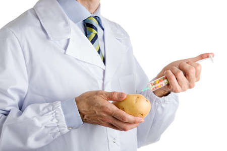 white coat: bust of a man wearing medical white coat, light blue shirt and glossy regimental tie white dark blue, light blue and green stripes, and makes an injection to potato Stock Photo