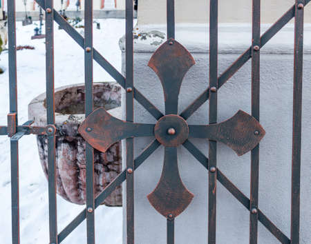 grey nails: rusty cross on iron gate of cemetery