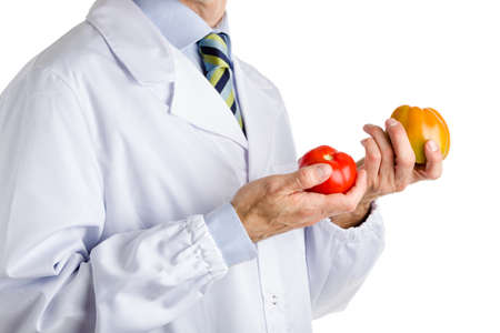white coat: bust of a man wearing medical white coat, light blue shirt and glossy regimental tie white dark blue, light blue and green stripes, and holding a red ripe tomato and a green one Stock Photo