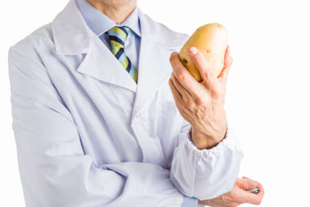 white coat: bust of a man wearing medical white coat, light blue shirt and glossy regimental tie white dark blue, light blue and green stripes, and showing a potato  with left hand