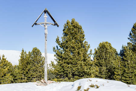 inri: A wood carved statue  of the Crucifixion of Jesus Christ on top of the dolomites alps Stock Photo
