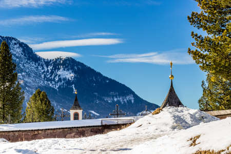 Catholic cemetery on high mountains overlooking snowy peaks and pine forest photo