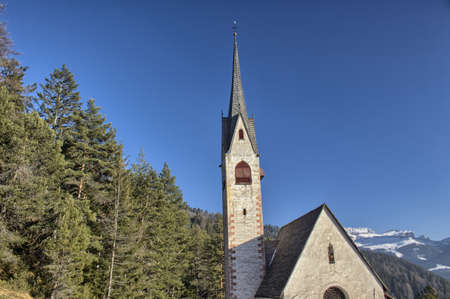 St. Jacob's Church overlooking pine forests and snow-capped peaks of Dolomites mountains in winter photo