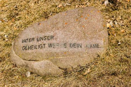 frase: Sentencia alemán de La Oración del Señor impreso en letras de molde en una roca en la hierba de invierno