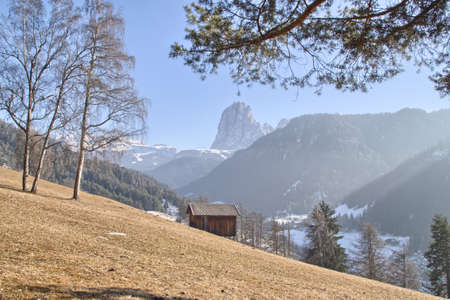 Mountain lodge on brownish orange grass in valley of pine forests and snow-capped peaks in winter