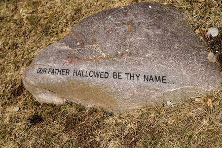 oracion: Sentencia de La Oraci�n del Se�or impreso sobre una roca en la hierba de invierno