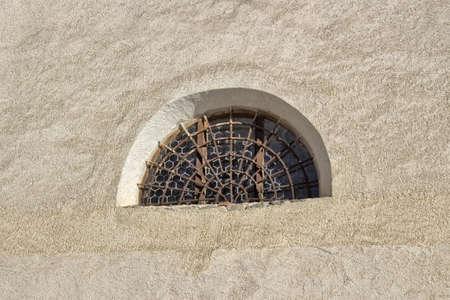 rejas de hierro: Ventana de piedra redondeada con rejilla de barras de hierro marrones oxidados en madera enmarcada vidrio con estructura hexagonal. Antiguo muro de color amarillo oscuro de la iglesia g�tica romano de San Jacob en Italia Foto de archivo
