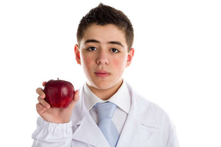 reminding: An acne skin child with medical white coat is showing a juicy and tasty red apple reminding of old saying, An apple a day keeps the doctor away, meaning the importance of a healthy diet since childhood. Stock Photo