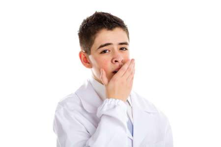 drowsiness: child dressed as a doctor in light blue tie and white coat helps to feel medicine more friendly: he is yawning while covering mouth with hand. His acne skin has not ben retouched