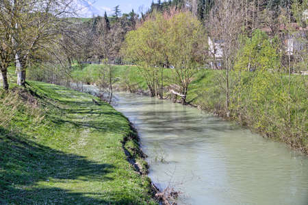 stillness: The tranquility of a quiet river in the countryside of the hills during spring in Northern Italy near Riolo Terme (Ravenna)