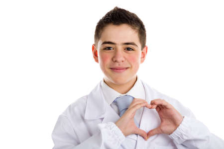 retouched: A child doctor in white coat helps to feel medicine more friendly making heart shape gesture with hands on his chest to point out heart care. His acne skin has not been retouched