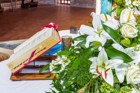 Antique Book on the altar for the celebration of Holy Mass in a Catholic Italian church with white flowers and green leaves as ornament