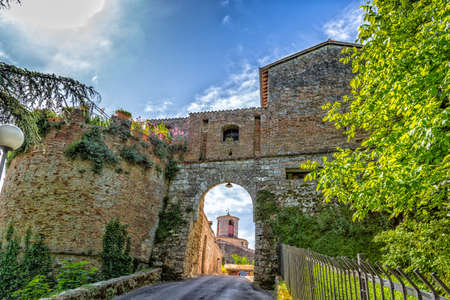 guarding: View through an ancient arch of a clock tower with brick walls guarding a countryside village in Italy Stock Photo