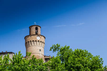 guarding: Clock tower with brick walls guarding a countryside village in Italy Stock Photo