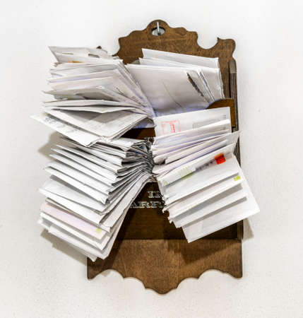 accounts payable: bunches of old bills and accounts  in dusty original envelopes collected in wood support