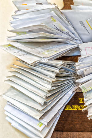 payable: bunches of old bills and accounts  in dusty original envelopes collected in wood support