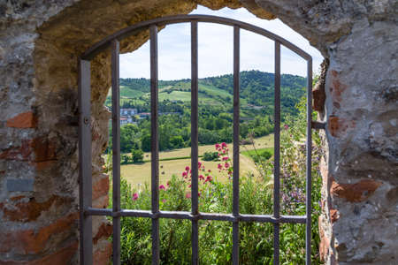 grating: Medieval window with iron grating overlooking the countryside of Romagna in Italy