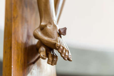 crucify: Detail of nailed feet in a wood carved statue  of the Crucifixion of Jesus Christ