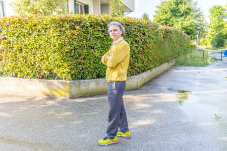 reassuring: Handsome middle-aged man with salt pepper hair, medium hair, dressed in casual clothing with yellow sweater, slacks blue and yellow sneakers in green outdoors: he shows a reassuring look crossing arms Stock Photo