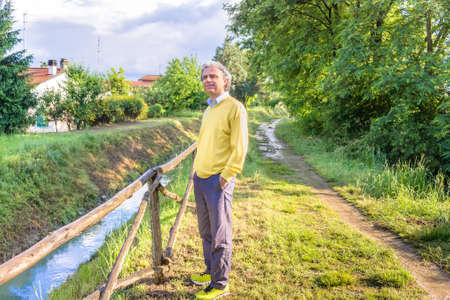 reassuring: Handsome middle-aged man with salt pepper hair, medium hair, dressed in casual clothing with yellow sweater, slacks blue and yellow sneakers in green outdoors: he shows a reassuring look holding hands in pocket