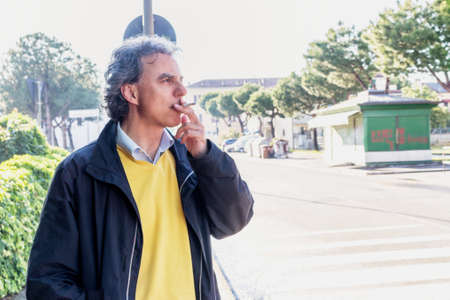 slacks: Handsome middle-aged man with salt pepper hair, medium hair, dressed in casual clothing with yellow sweater, slacks blue and yellow sneakers in green outdoors: he is smoking a cigarette