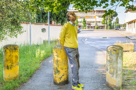reassuring: Handsome middle-aged man with salt pepper hair, medium hair, dressed in casual clothing with yellow sweater, slacks blue and yellow sneakers in green outdoors: he shows a reassuring look while seating on bollard Stock Photo