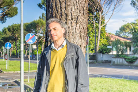 reassuring: Handsome middle-aged man with salt pepper hair, medium hair, dressed in casual clothing with yellow sweater, slacks blue and yellow sneakers in green outdoors: he shows a reassuring look leaning with back to a tree