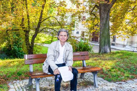 hombre viejo: Apuesto hombre de 50 a�os con el pelo sal pimienta y ojos verdes vestidos con gabardina gris, camisa blanca de lino y pantalones azules est� leyendo documentos en un parque en Praga